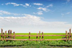 Wooden fence on green meadow. With a great blue sky background stock image