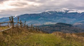 Wooden fence on hills of mountainous countryside. Agricultural fields in late autumn gloomy weather. mountain ridge with snowy tops in the distance Royalty Free Stock Images
