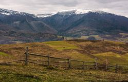 Wooden fence on hills of mountainous countryside. Agricultural fields in late autumn gloomy weather. mountain ridge with snowy tops in the distance Royalty Free Stock Photography