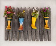 Wooden fence decoratet with flowers planted in rubber boots. Wooden fence on a house wall decorated with different flowers planted in colorful rubber boots Royalty Free Stock Photography