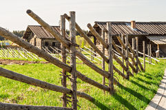The wooden fence of the individual logs. Wooden fence from a separate logs , enclosing a plowed field Royalty Free Stock Image