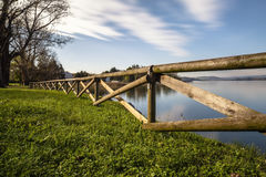 Wooden fence. A wooden fence installed to protect people from falling into the lake when walking on the grass royalty free stock images