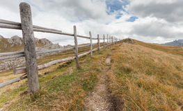 Wooden fence long a path in Val di Funes Royalty Free Stock Photo