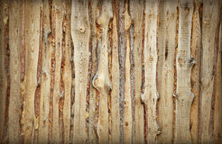 Wooden fence made of boards and slabs - background. Coarse rural wooden fence made of boards and slabs - the background stock images