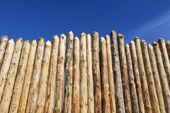 Wooden fence made of sharpened planed logs. Wooden fence made of sharpened planed logs Royalty Free Stock Image