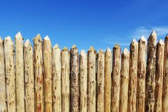 Wooden fence made of sharpened planed logs. Wooden fence made of sharpened planed logs Royalty Free Stock Photos