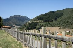 Wooden fence in a meadow with the mountains of asturias in the background on a sunny day stock image