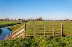 Wooden fence and a meandering ditch royalty free stock image