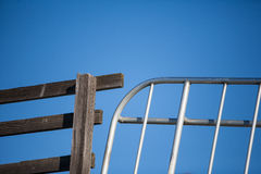 Wooden fence and metal gate juxtaposed against blue sky. Wooden fence and metal gate side by side with blue sky behind Royalty Free Stock Image