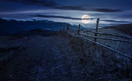 Wooden fence in mountainous countryside at night. In full moon light. mountain ridge with snowy tops in the distance Stock Photos
