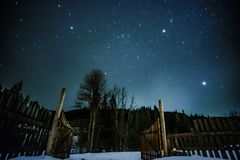 Wooden fence in mountains with starry sky above stock photo
