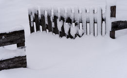 Wooden fence and open gate in deep snow. Wooden fence and open gate covered in deep snow in winter in the Alps in Switzerland Royalty Free Stock Photography