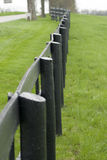 Wooden fence over green field Stock Photography