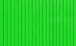 Wooden fence with parallel planks with green paint. Stock Image