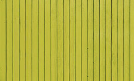 Wooden fence with parallel planks with yellow paint. Royalty Free Stock Images