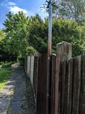Wooden fence and pathway. A brown wooden fence next to a concrete pathway in the garden stock image