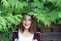 Girl covered with green tree branches in front of wooden fence. Wooden fence photoset. Girl covered with green tree branches in front of wooden fence Royalty Free Stock Photo