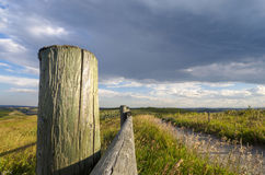 Wooden fence in the prairies on a ranch on a rainy day. Pretty Wood Fence during the golden hour as storm clouds roll in Royalty Free Stock Photography