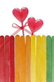 Wooden fence in rainbow colors and two lollipops in heart shape Royalty Free Stock Photo