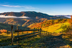 Wooden fence by the road in rural area. Autumn countryside landscape in mountains with grassy fields. beautiful misty sunrise stock image