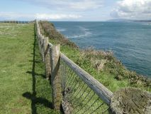 Wooden fence on rocky headlands and surf Stock Photography
