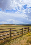 Wooden fence on a rural farm pasture fields. On a beautiful sunny day with clouds and blue sky Royalty Free Stock Photos