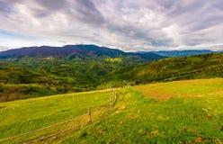 Wooden fence through rural field on hillside Stock Photos