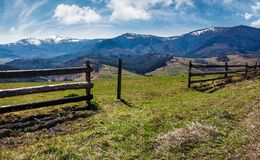 Wooden fence on rural hill in spring. Lovely mountainous landscape with snowy peaks in the distance Royalty Free Stock Photo