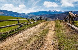 Wooden fence on rural hill in spring. Lovely mountainous landscape with snowy peaks in the distance Royalty Free Stock Image