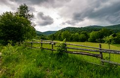 Wooden fence on a rural meadow in mountains. Lovely agriculture scenery on a cloudy summer day Stock Photography
