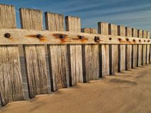 Wooden fence in sand. On beach royalty free stock images