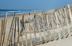 Wooden fence and sandy beach. Wooden fence with beach, people and sea in background Stock Photos