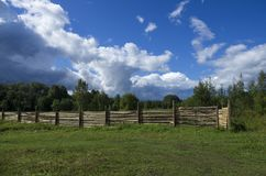 Wooden fence set in a forest area. In the background of a blue sky with clouds stock photos