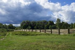 Wooden fence set in a forest area next to a rural road. In the background blue sky with clouds royalty free stock photography