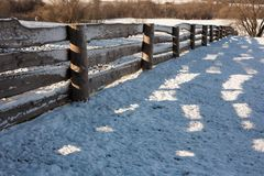 Wooden fence with shadows from a farm in winter.  Royalty Free Stock Photography