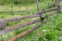 A wooden fence in a small detached mountain village. An old wooden fence in a small detached village in Carpathian mountains, Ukraine. Everything is covered with stock images