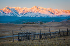Wooden fence in snow covered mountains. Under shiny sun Royalty Free Stock Images