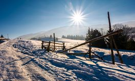Wooden fence on snowy meadow. Lovely rural scenery on a bright sunny day. location Pylypets, Ukraine Stock Image