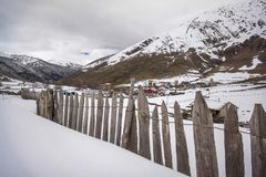 Wooden fence on snowy meadow stock images