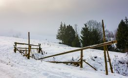 Wooden fence on snowy meadow. Lovely rural scenery on a foggy morning. location Pylypets, Ukraine Royalty Free Stock Image