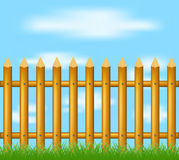 Wooden fence standing in grass and blue sky. With clouds Royalty Free Stock Photo