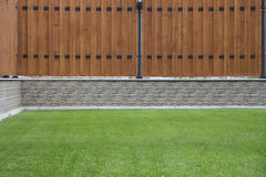 Wooden fence with stone basic and green grass in front. Stock Image