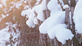Wooden fence under snow. In backlit sunshine wooden fence under snow stock video footage