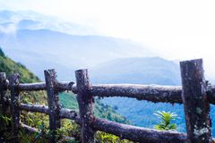 Wooden fence at view point mountain background. Old wooden fence with mountain and white cloud background Stock Photo