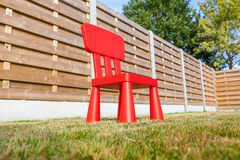 Wooden fence whit chair. A fence is a freestanding structure designed to restrict or prevent movement across a boundary. Fences are generally distinguished from Stock Photography