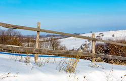 Wooden fence on winter meadow. Wooden fence on winder meadow in sunny day Stock Image
