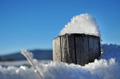 Wooden fence in winter with snow and ice crystals Stock Photos