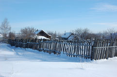 Wooden fence in winter village. View of small snowy russian village with old wooden fence at winter sunny day Royalty Free Stock Photo