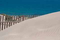 Wooden fences on deserted beach dunes in Tarifa, Spain Royalty Free Stock Photo