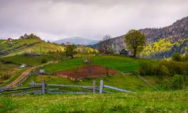 Wooden fences of rural area on grassy hillsides. Lovely rural landscape of mountainous village in springtime Stock Photo